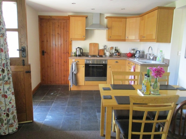 The cottage has a well equipped kitchen and dining table seating four people.