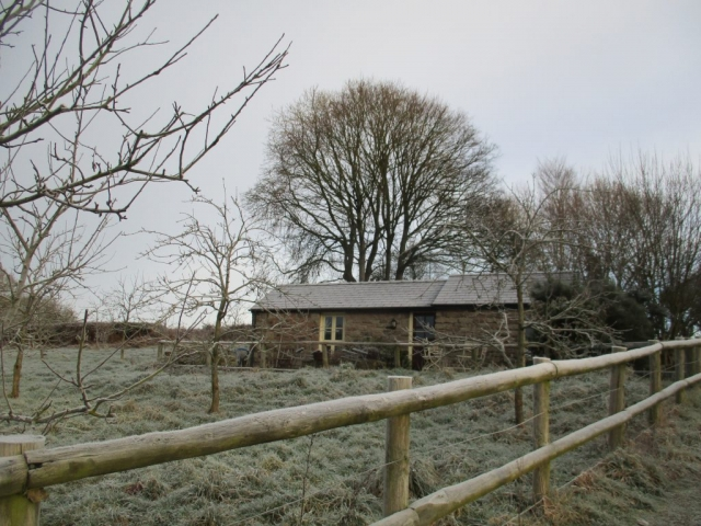 Cottage in winter with bare trees in the orchard
